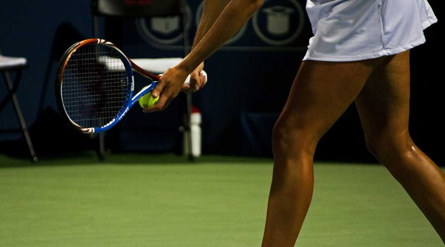 Female tennis player about to serve.
