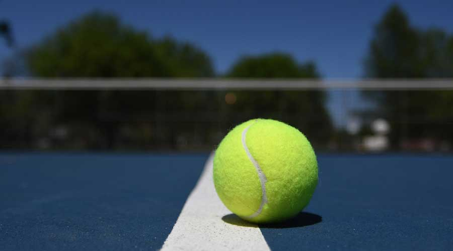 Tennis ball on the line of a tennis court.
