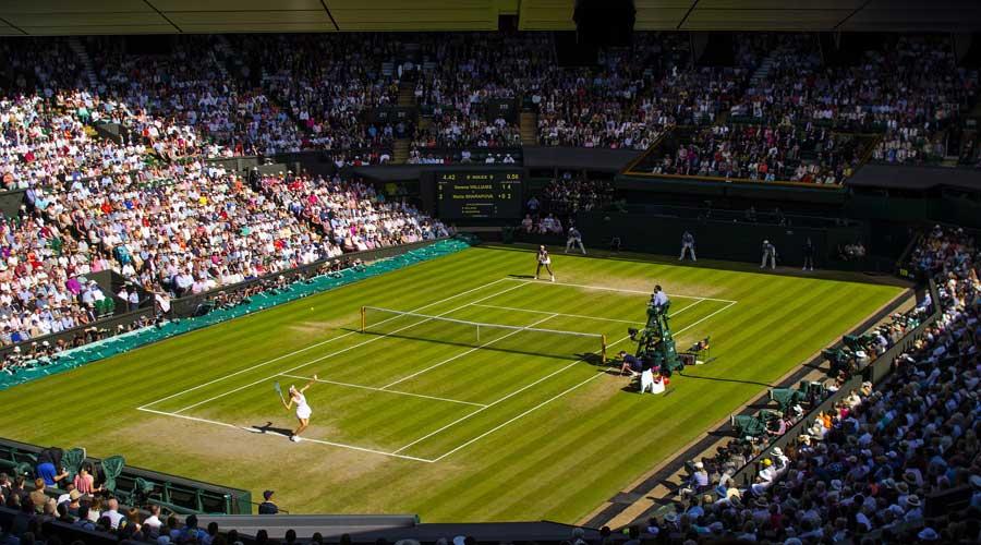 Tennis match being played on grass at Wimbledon.