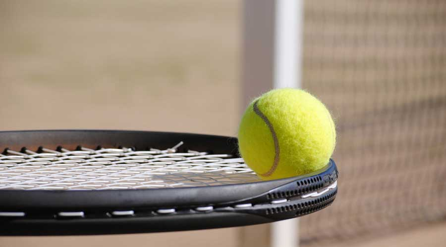 Tennis ball on a racquet.