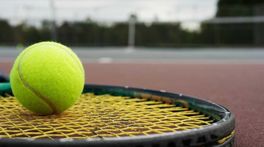 Tennis ball resting on a racquet.